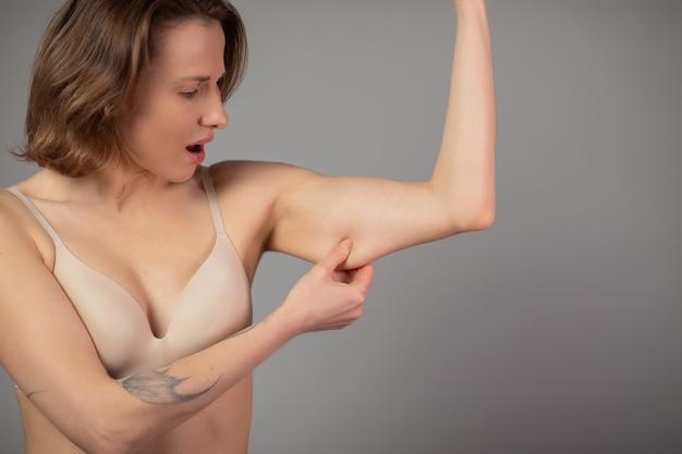 減量のコンセプトです。灰色に分離された上腕の脂肪をつまんでぽっちゃりした女性。 Premium写真
