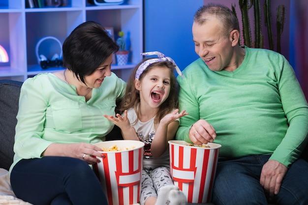 面白い高齢者の古い家族と小さな子供孫娘がソファーに座っているとポップコーンを食べてテレビを見て Premium写真