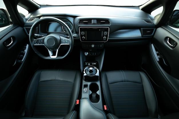 ドアのハンドルの電気自動車内部の詳細。窓のコントロールと調整。フロントシート、運転席と助手席、テキスタイル、窓、ドアパネル、コンソールを備えた車内 Premium写真