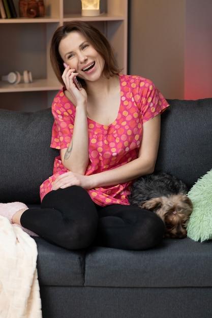 自宅の電話で話している幸せな陽気な若い女性。ソファに座って携帯電話で電話に出る笑顔の女性。携帯電話で話して楽しい面白い会話をしている美しい女性。 Premium写真