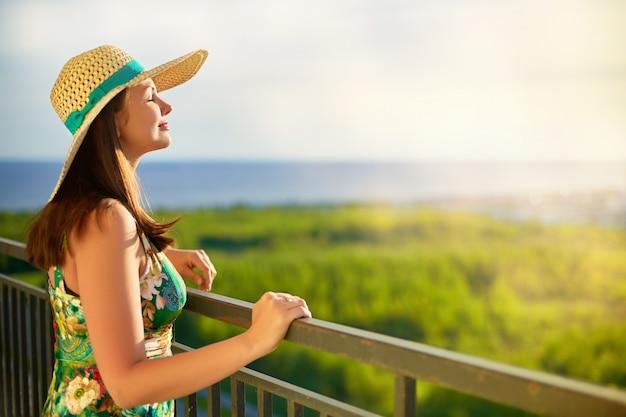 海を見ている帽子をかぶっている女性 Premium写真