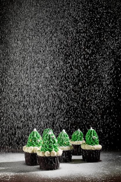 Зеленые пирожные с добавлением белого крема в виде елки в разном порядке посыпают сахарной пудрой Premium Фотографии