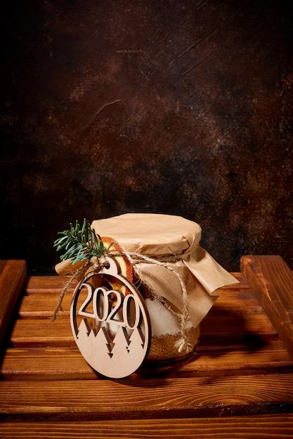 Баночка, полная сладких специй, покрыта крафт-бумагой и обвязана шпагатом, к нему привязан медальон с цифрами нового года, стоящий на деревянном поддоне Premium Фотографии