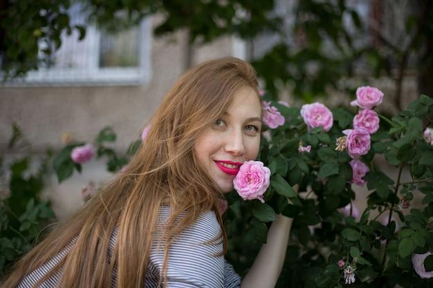 ピンクのバラの茂みの近くに一人で座っていると笑顔の美しい赤い髪の少女 Premium写真