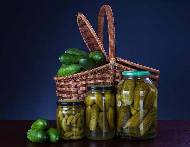 瓶に缶詰のキュウリとバスケットに新鮮なキュウリ Premium写真