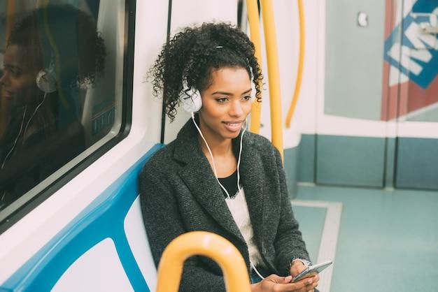 音楽を聴く地下の中に座って幸せな若い黒人女性 Premium写真