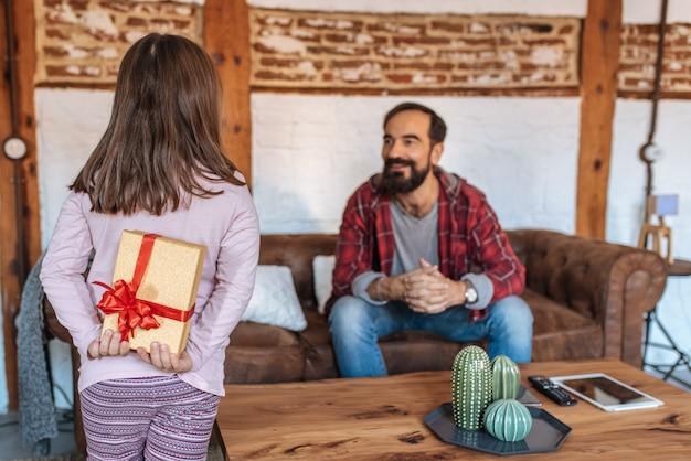 Маленькая девочка делает подарок своему отцу на диване у себя дома в день отцов Premium Фотографии