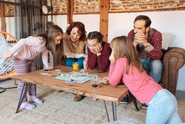 古典的なテーブルゲームをプレイしてソファで自宅で幸せな家族 Premium写真