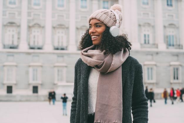 音楽を聴くと冬の王宮近くの携帯電話で踊る若い黒人女性 Premium写真