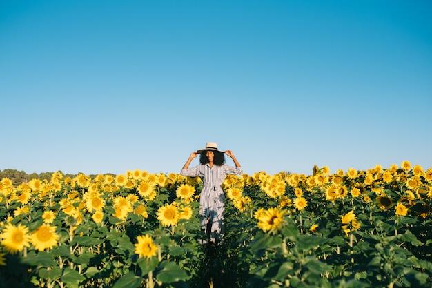 Счастливая молодая чернокожая женщина гуляя в поле солнцецвета Premium Фотографии