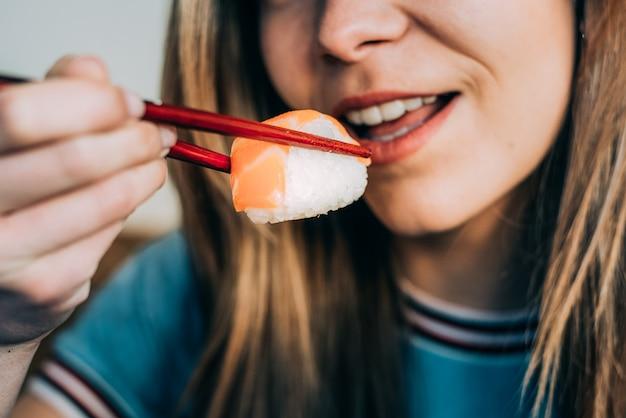 Урожай женщина ест суши Premium Фотографии