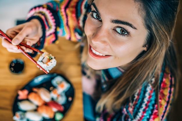 Сверху посевная женщина ест суши Premium Фотографии