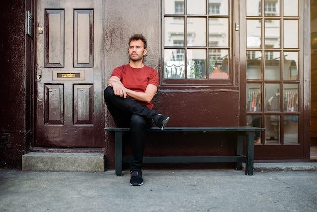 Человек сидит в скамейке на фоне красивых бордовых Premium Фотографии