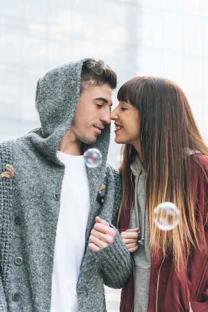 石鹸の泡でロマンチックな方法で通りの真ん中でお互いを抱いて愛のカップルで美しい若い Premium写真