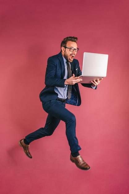 Бизнесмен с компьютерным прыжком Premium Фотографии