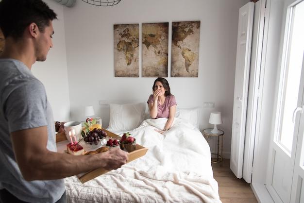 Молодая пара дома с завтраком в постели сюрприз Premium Фотографии