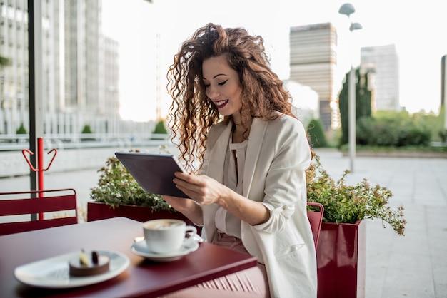 タブレットの若いビジネス赤毛の女性 Premium写真