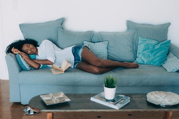Красивая черная молодая женщина спит на диване Premium Фотографии