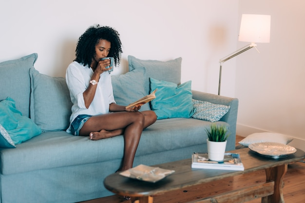 Красивая молодая негритянка сидения на диване, почитать книгу и пить кофе Premium Фотографии