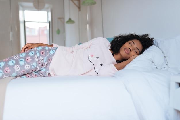 Счастливая красивая молодая чернокожая женщина лежа в кровати спать Premium Фотографии