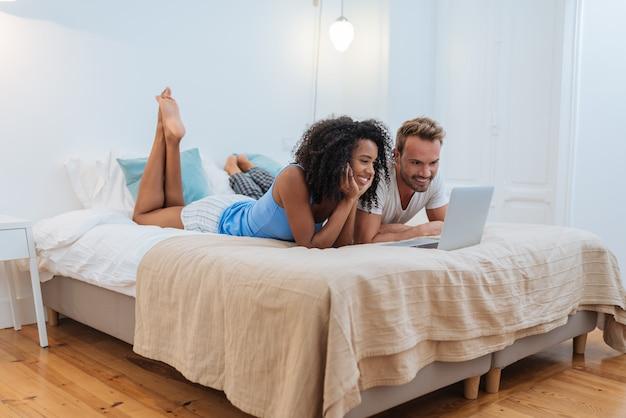 幸せな若いカップルが自宅のコンピューターでベッドに横たわってリラックス Premium写真