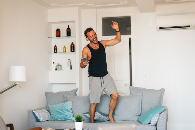 音楽を聴くと踊りの携帯電話で自宅でソファに立っている幸せな若い金髪男 Premium写真