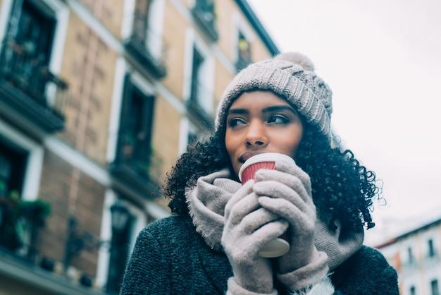 冬にマドリードの街をさまようコーヒーを飲む若い黒人女性 Premium写真