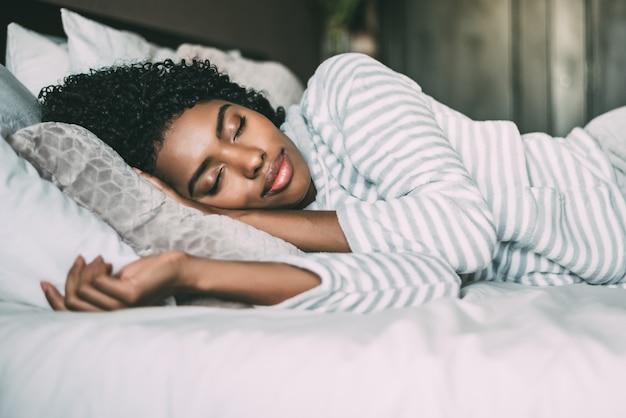 Крупным планом довольно черная женщина с вьющимися волосами, спать в постели с закрытыми глазами Premium Фотографии