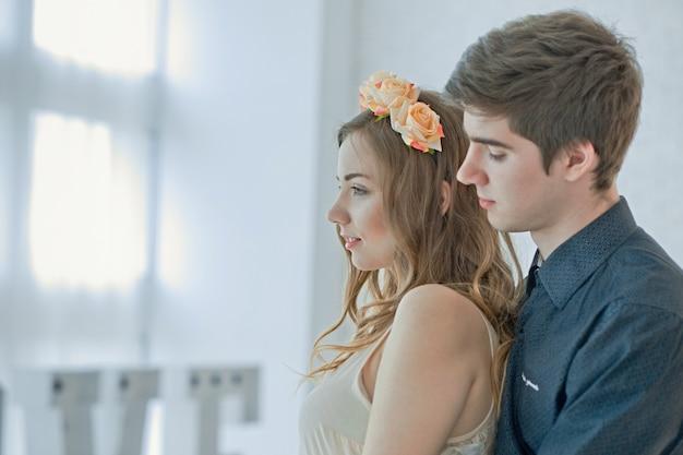 男は女の子を後ろから抱擁します。晴れた日に光の大きな窓に対する愛のカップル。 Premium写真