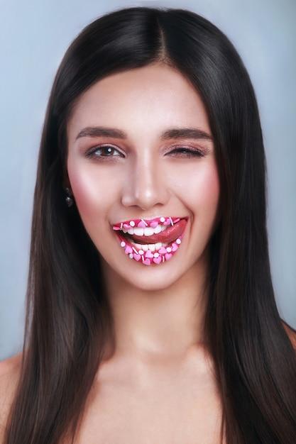 バレンタインハートの甘いメイク。バレンタインデーのメイクアップの唇にピンクのハートの砂糖を振りかけます。唇にキスする。 。バレンタイン・デー。 Premium写真