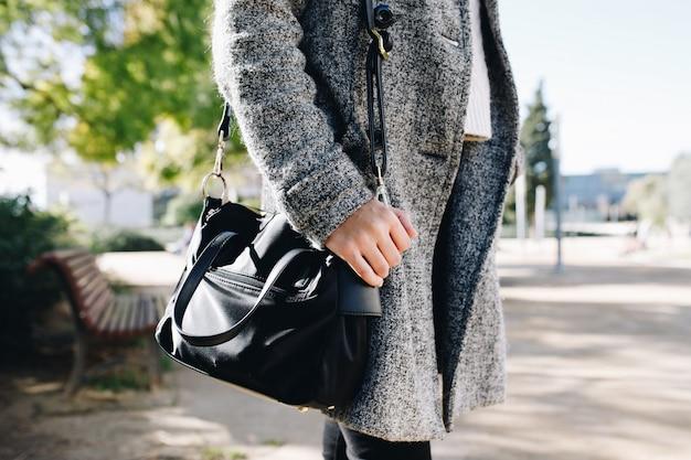 女性を着て、秋のコレクションでコートと財布でポーズ Premium写真