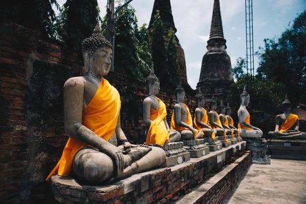 アユタヤの古代都市のタイ北部の寺院のいくつかの彫刻の仏背景 Premium写真
