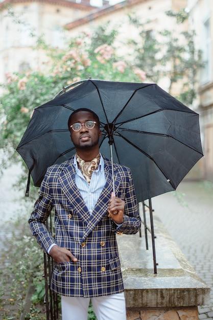 フォーマルな服を着た黒い傘の下で曇りの天候で市内中心部に立っているハンサムなアフリカ系アメリカ人実業家の都市の肖像。 Premium写真
