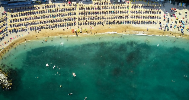 Вид с воздуха на песчаном пляже с туристами, купание в красивой чистой морской воде. солнечный берег вид сверху. летнее время - море, песок, зонтики, полотенца, стулья, туристы, катер и парусник. Premium Фотографии