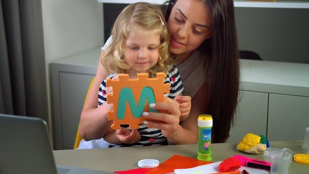Кавказская женщина с длинными черными волосами и ее маленькая дочь со светлыми вьющимися волосами, ваяющие с пластилином на фоне живой. в помещении. Premium Фотографии