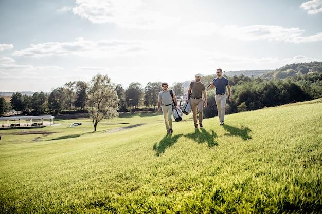 Игрок в гольф, идущий и несущий сумку на поле во время игры в гольф летом Premium Фотографии