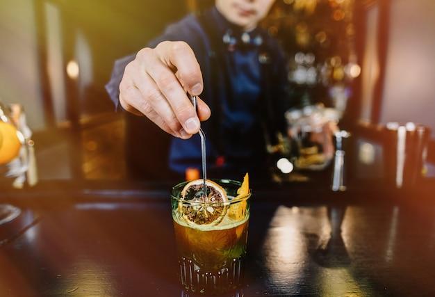 Эксперт бармен делает коктейль в баре. Premium Фотографии