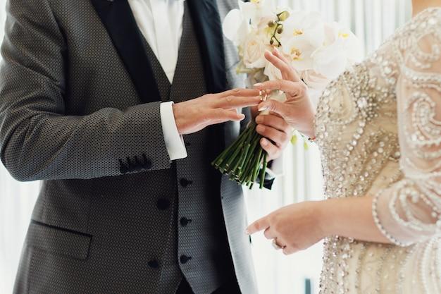 Жених и невеста с обручальным кольцом и букетом свежих цветов Premium Фотографии