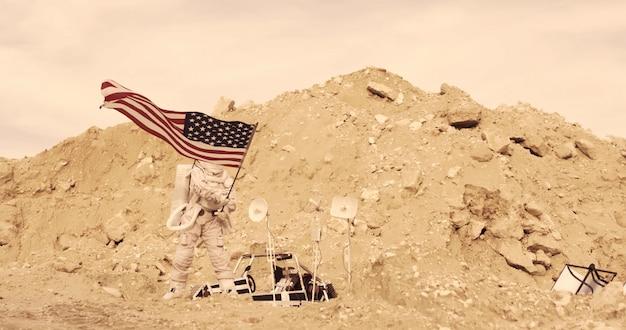 エイリアンレッドプラネット/火星のロッキーマウンテンに立っているアメリカの国旗を持つ宇宙飛行士。火星の最初の有人ミッション Premium写真