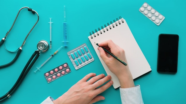 医学、医療、人々の概念。メモ帳、聴診器、薬、医師の机で注射器と医学の職場 Premium写真