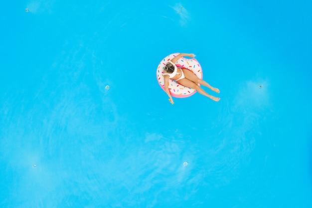 プールで膨脹可能なドーナツでリラックスした白いビキニの美しい少女の空撮。夏休みの背景 Premium写真