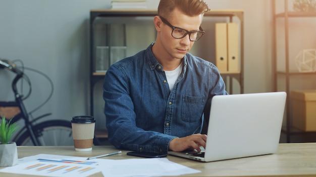 Деловой человек работает в офисе с ноутбуком и с помощью телефона Premium Фотографии