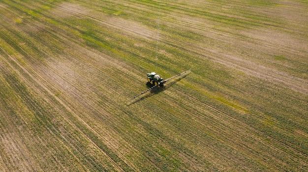 Аэрофотоснимок распыления машины, работающие на зеленом поле. Premium Фотографии