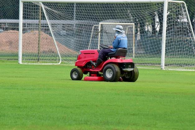 芝刈り機と草刈りの世話をするドライバーとサッカースタジアムは常に見えます Premium写真