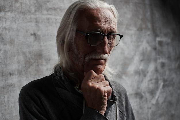 高齢者の灰色の髪の白人は人生を考えて引退した男。口ひげと思慮深い表情のメガネの祖父は彼のあごを保持 Premium写真