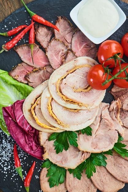 冷たい肉ローストビーフ、焼きハム、チキンロール、牛タンの平面図、石の板で提供 Premium写真