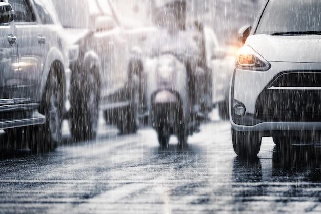 ぼやけた車で街中にひどい雨が降ります。セレクティブフォーカスと色調。 Premium写真