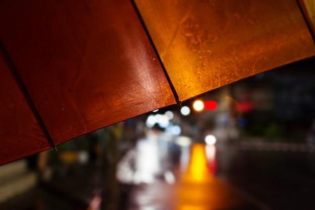 傘、夜の強い雨、選択的な焦点と色調。 Premium写真