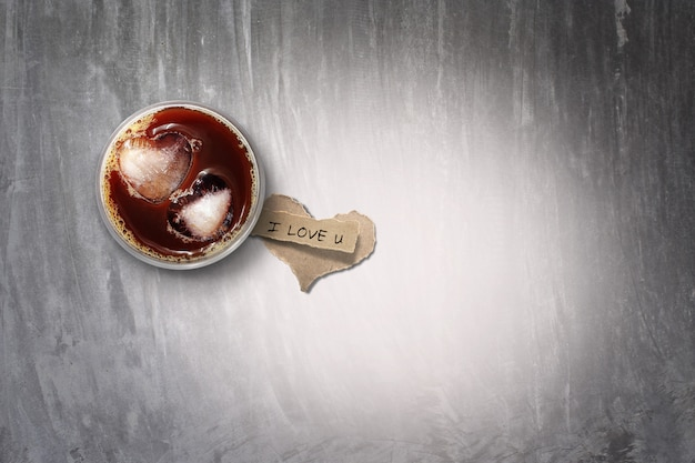 アイスコーヒーと引き裂かれた紙のコンクリートの床、色のトーン。バレンタインデーに。 Premium写真