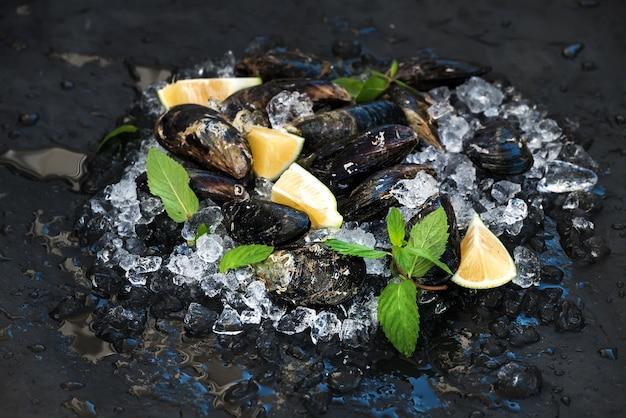 暗いスレートの石の背景の上の砕いた氷の上にレモン、ハーブ、スパイスを加えた新鮮な生ムール貝 Premium写真